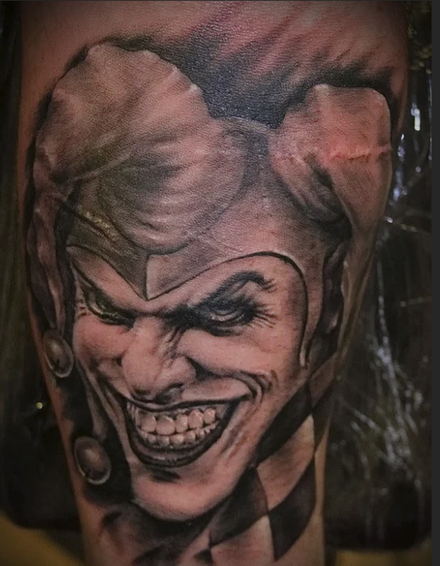 a tattoo of the evil joker from the cards