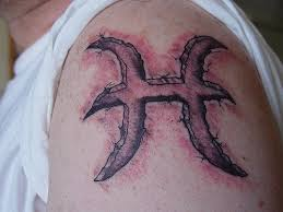 tattoo of the zodiac sign of the fish on the shoulder