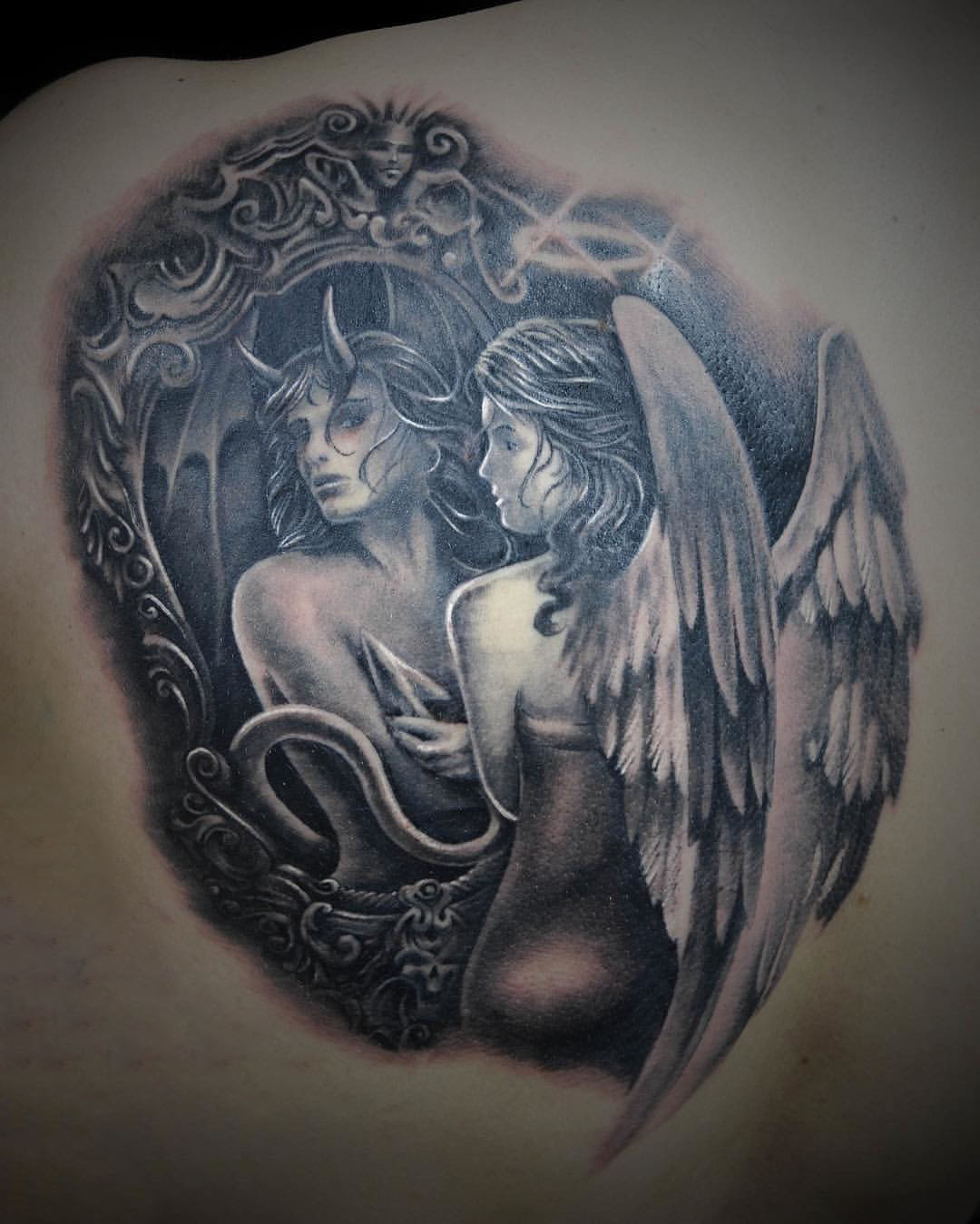 tattoo of the reflection of an angel and a demon