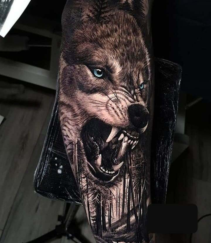 tattoo of a wolf on a guy's arms