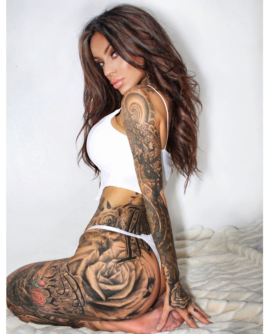 beautiful mulatto with tattoos poses for the photographer